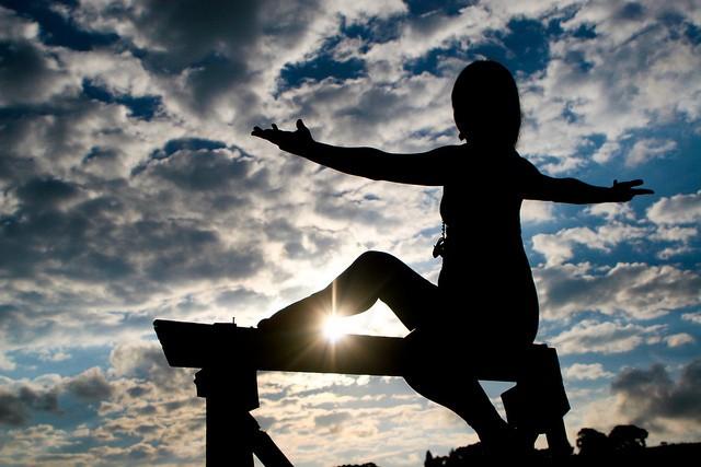 Femme pratiquant le yoga, sport bien-être, sur fond de ciel ponctué de nuages.