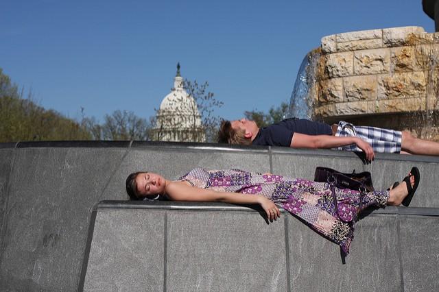 Deux personnes font la sieste près d'une fontaine.