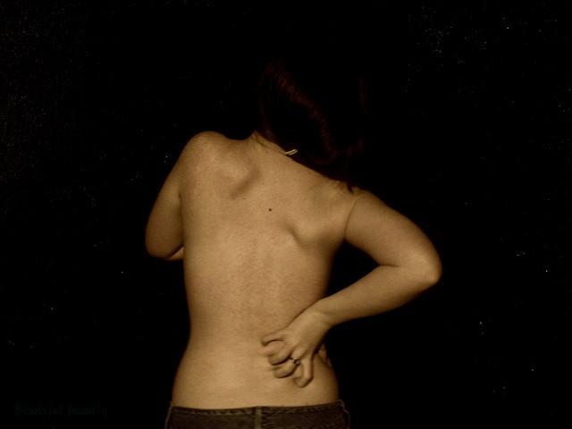Femme qui a mal au dos, un grand dossier d'ergonomie.