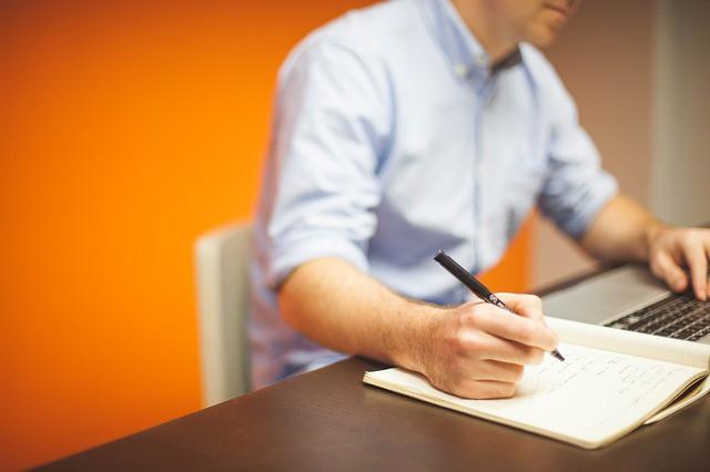 Homme assis de façon ergonomique à un bureau en train d'écrire.