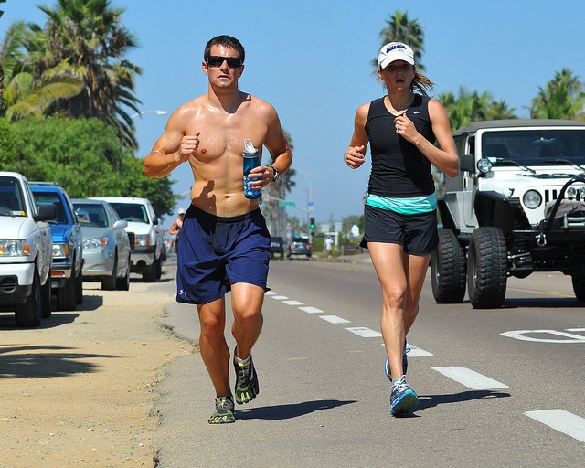 Un couple de runners en bord de route par beau temps.