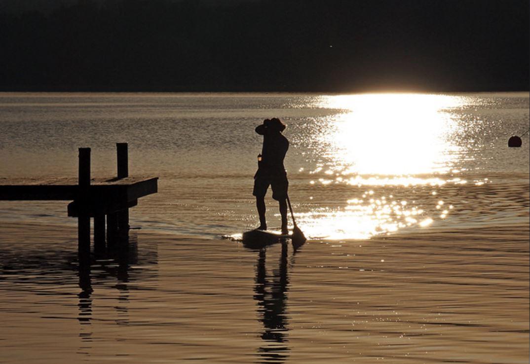 Un homme fait du Paddle board au couché du soleil