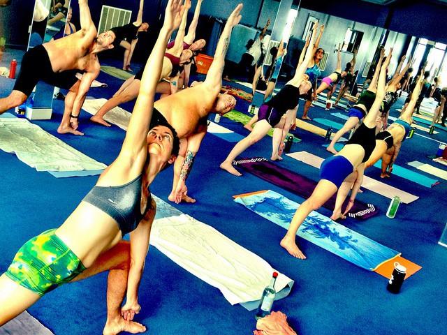 Groupe de participants à un cours de Bikram yoga, avec chacun un tapis, une bouteille d'eau et une serviette.