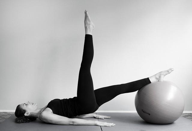 Une femme fait des exercices de Pilates.