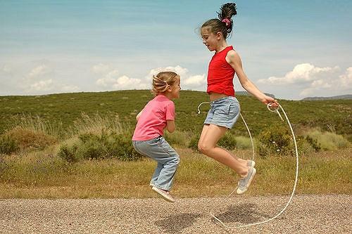 Deux fillettes sautent à la corde.