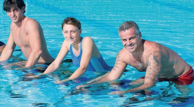 Trois personnes pratiquent l'aquabike, exercice d'aquagym.