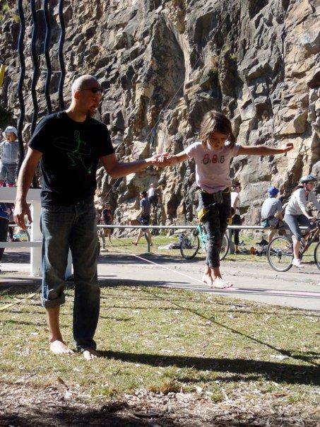 Ugo Capozzoli guide une petit fille sur une slackline d'initiation.