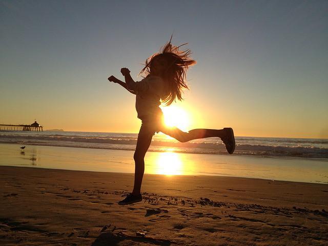 Afrovibe sur la plage, une participante saute devant le soleil couchant.
