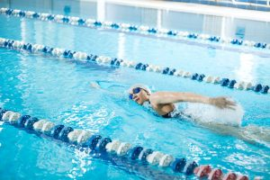 Une femme pratique la crawl en piscine
