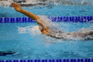Une femme pratique le dos crawlé en piscine