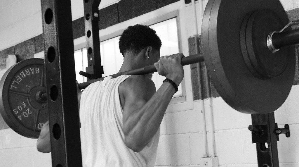 un homme faisant du squat dans le cadre de sa préparation physique générale