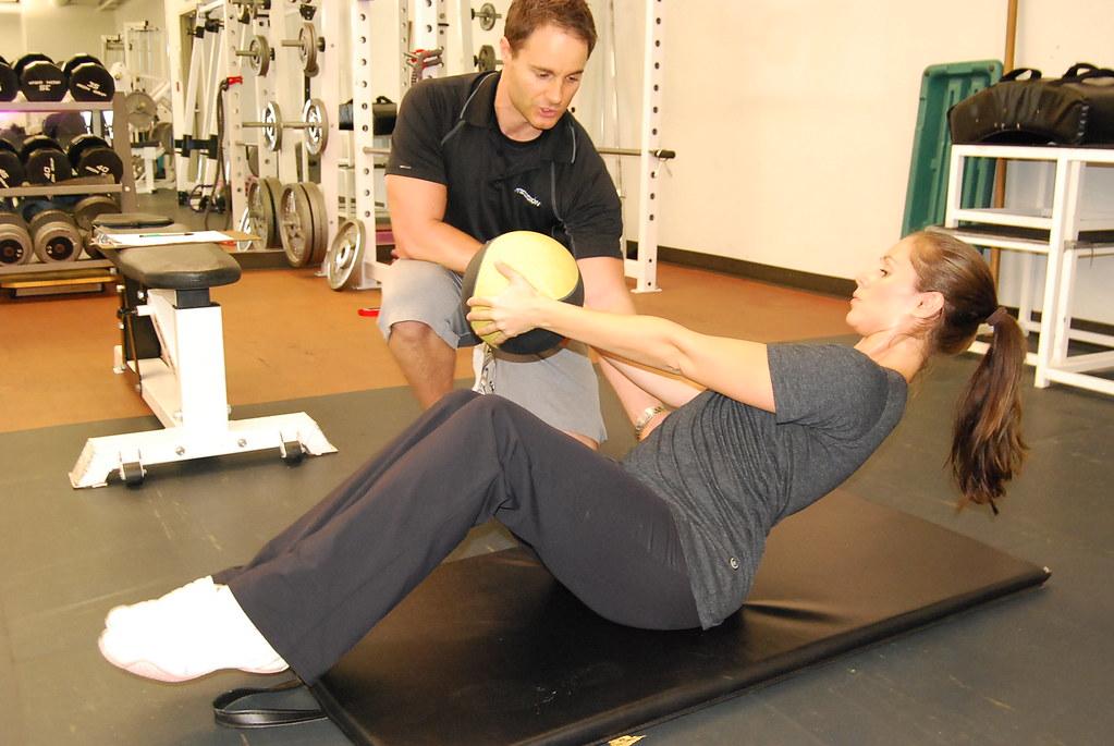 Une femme fait du core-training avec un coach sportif
