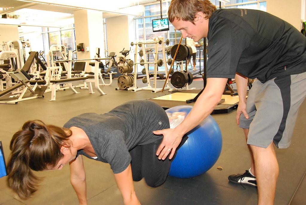 Un coach sportif et sa cliente en train de faire une séance d'abdominaux