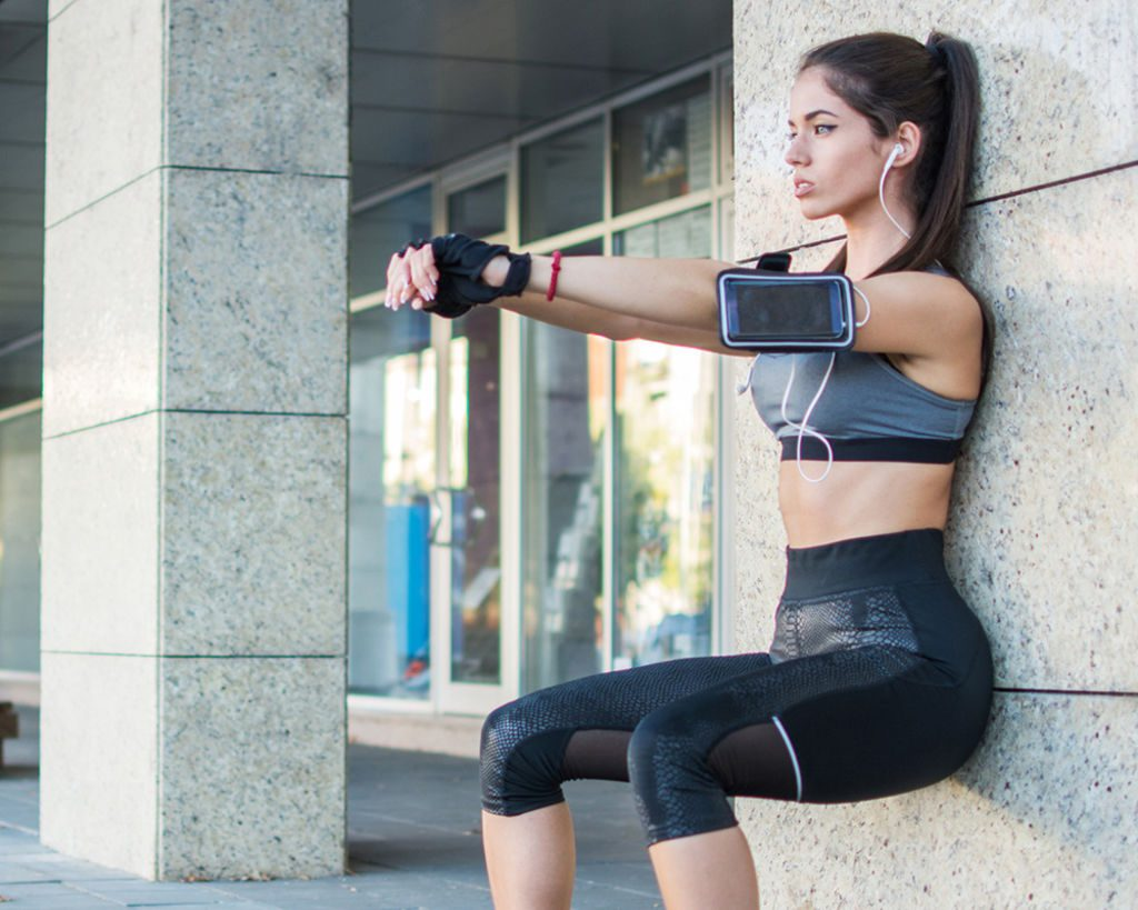 préparation physique pompiers : une jeune femme réalisant l'exercice de la chaise pour renforcer ses quadriceps