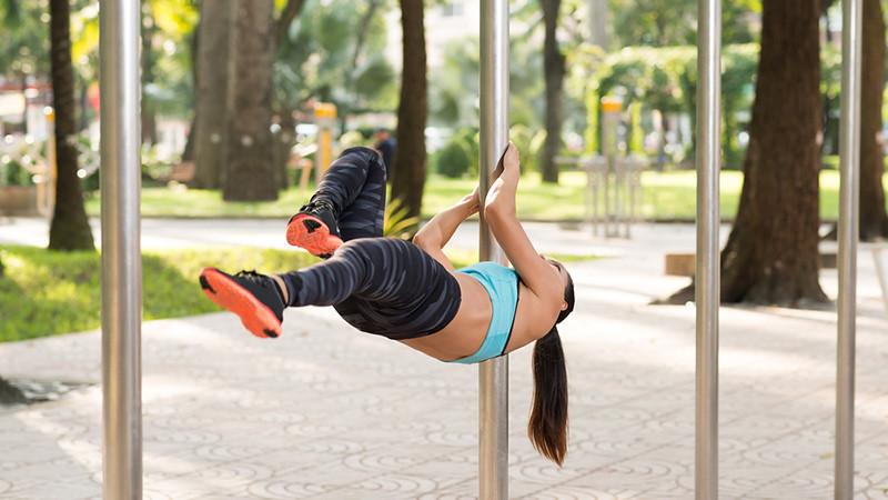 Une femme fait un dragon fly sur une air de street workout