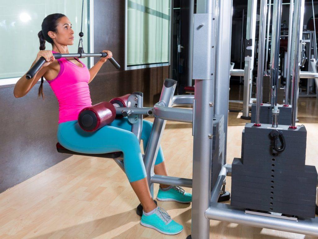 Une femme s'entraine avec un appareils de musculation avec poulie