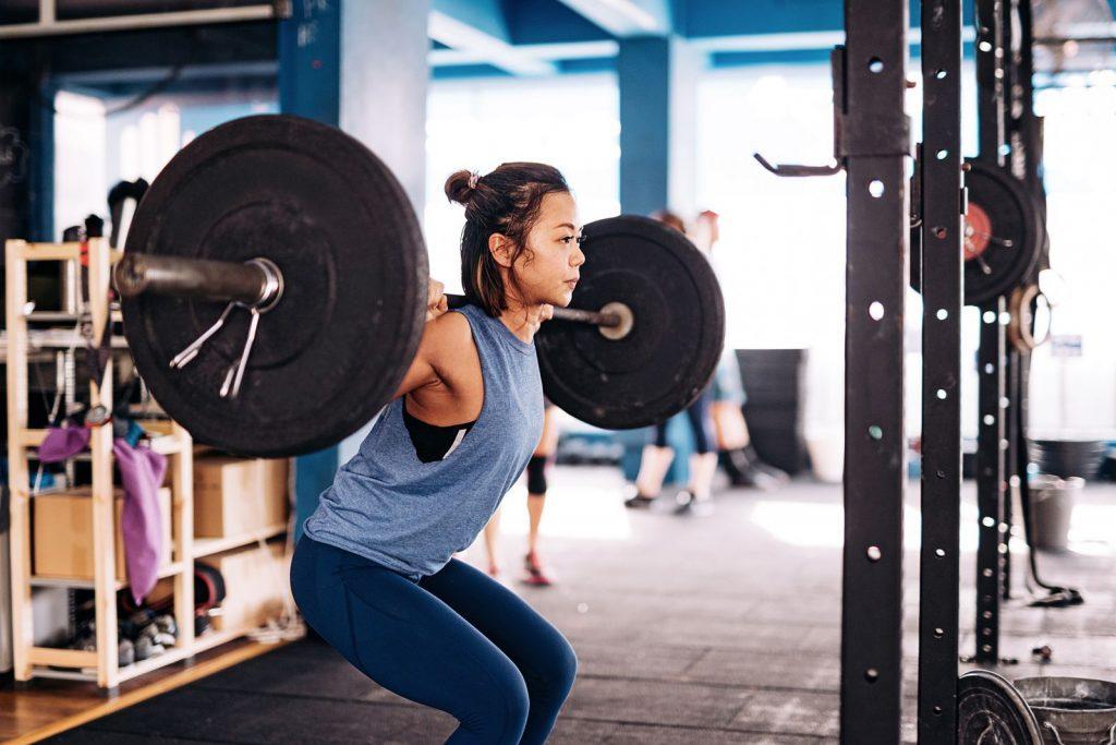 Une femme devant un rack de musculation en train d'effectuer des squats