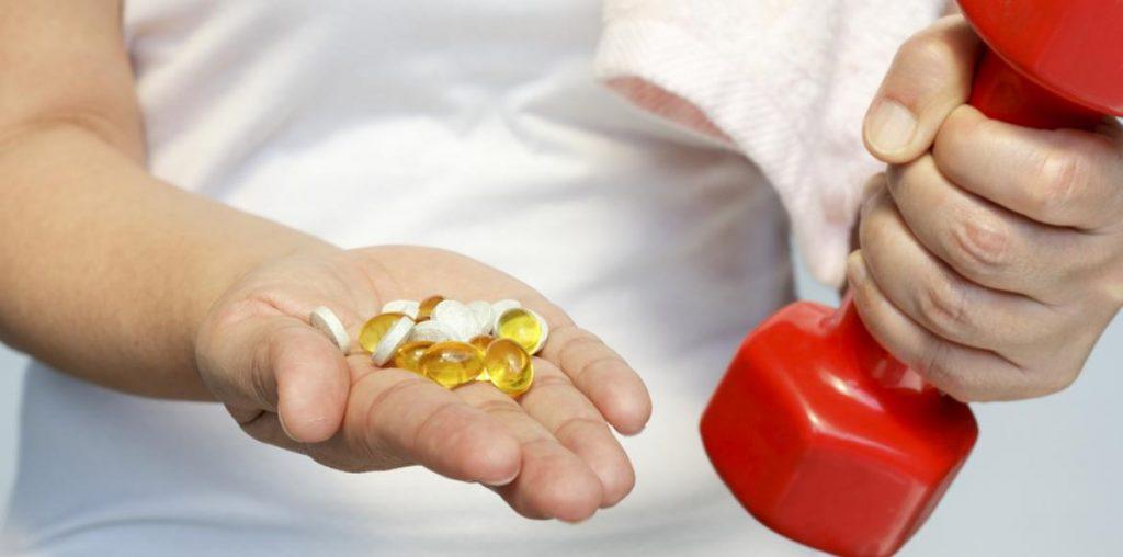 Une femme tient une altère et des médicaments contre l'hypertension