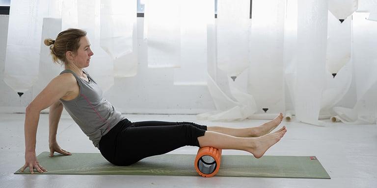 un femme se masse avec un foam roller