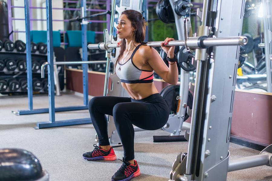 Une femme s'entraine avec une barre guidée