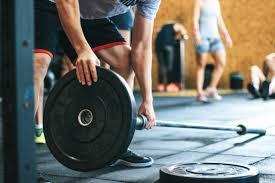 Un homme charge des poids de musculation sur une barre de musculation