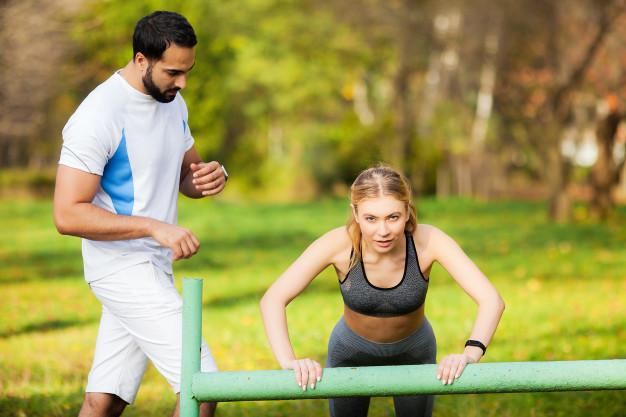 Une femme avec son coach sportif en séance de HIIT