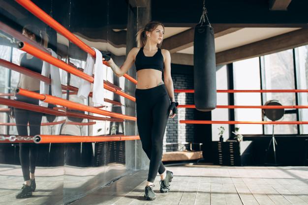 Femme dans un ring avant une séance de cardio boxing