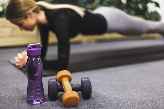 Une femme en position gainage sur un tapis de yoga