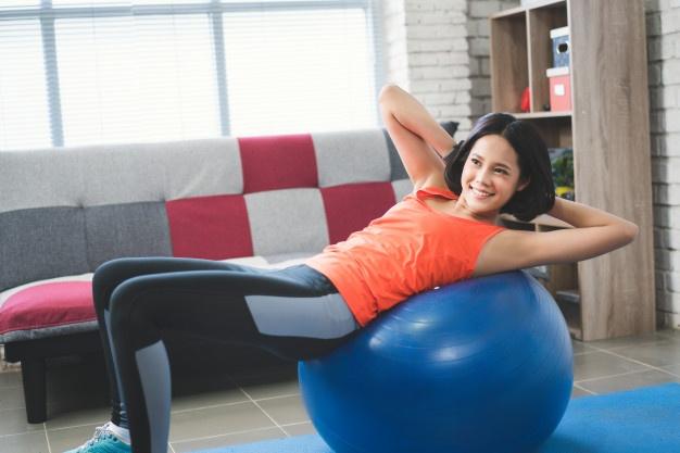 Une femme fait du renforcement musculaire sur un swiss ball