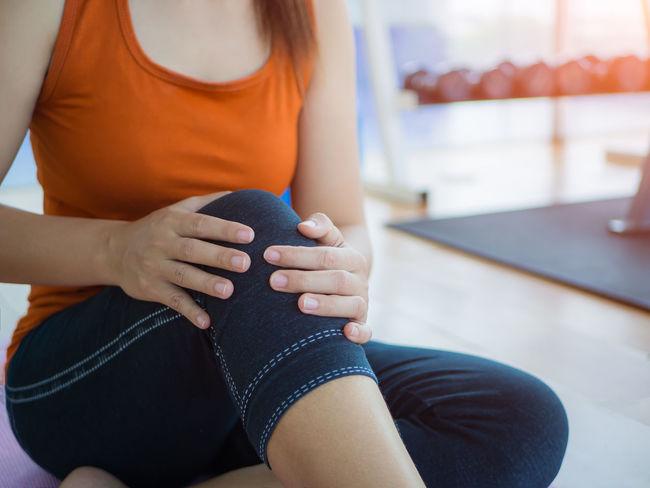 Une femme avec des douleurs au genou suite à une séance de fitness