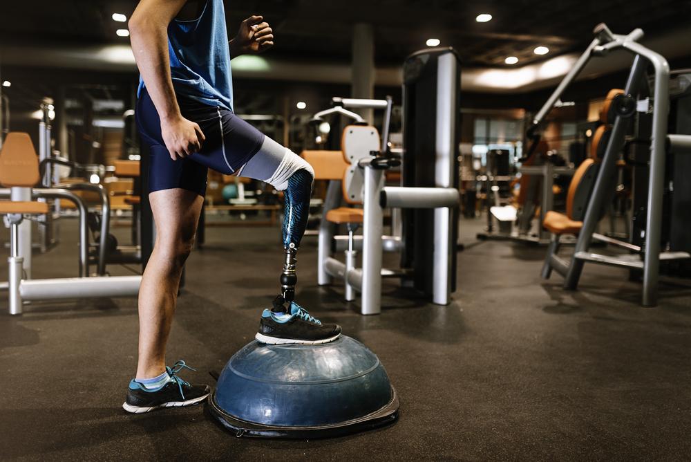 Un homme souffrant de handicap s'entraine avec un bosu en salle de sport