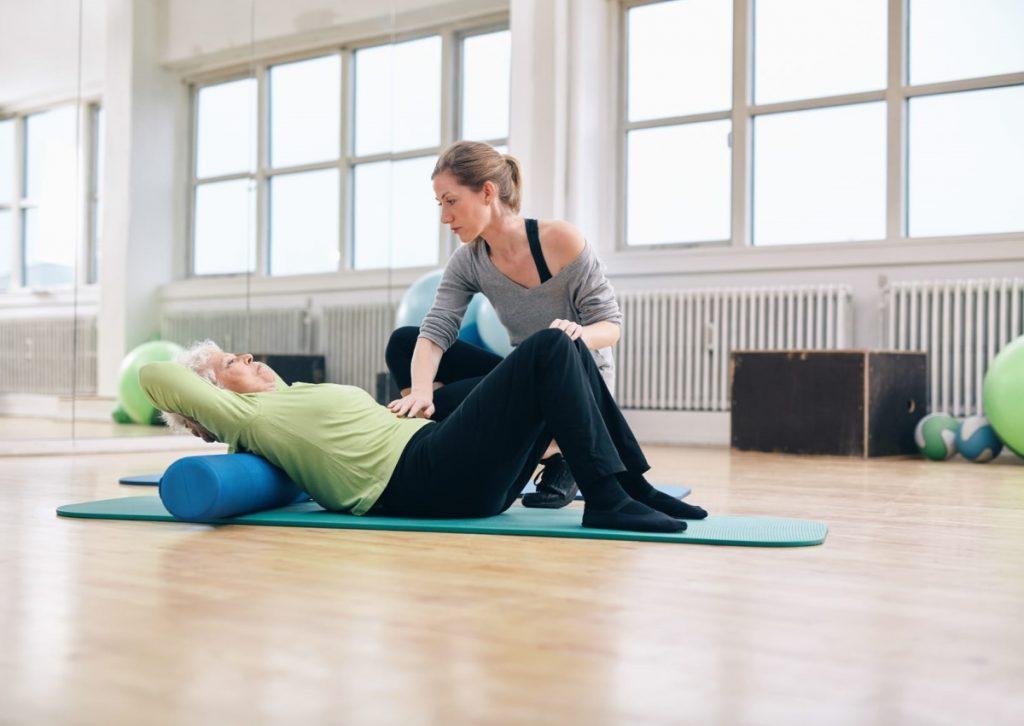 Une senior et son coach en séance de yoga