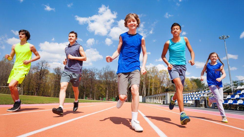 Un groupe d'enfant courent sur une piste d'athlétisme