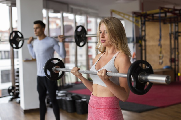 Une femme et un homme pratiquant le body pump