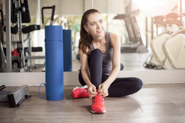 Femme en train de lasser ses chaussures de fitness