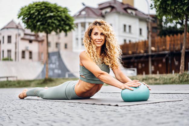jeune femme en train de pratiquer la gymnastique avec un balle souple lesté