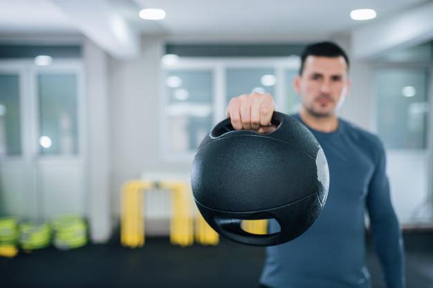 coach présentant un exemple de balle lestée : le Médecine Ball