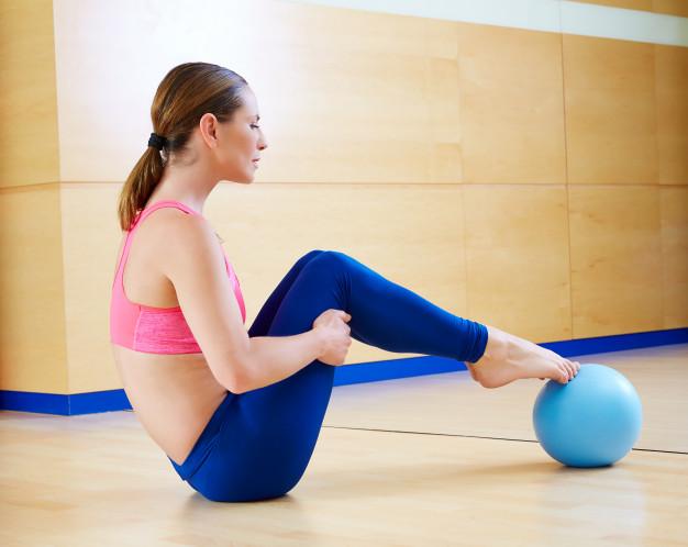 femme réalisant l'exercice du Curl ischio jambiers avec une balle lestée