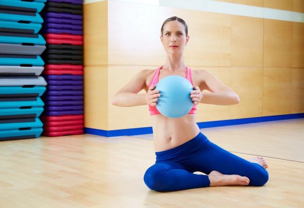 exercice de pilates : la Presse frontale avec une balle lestée