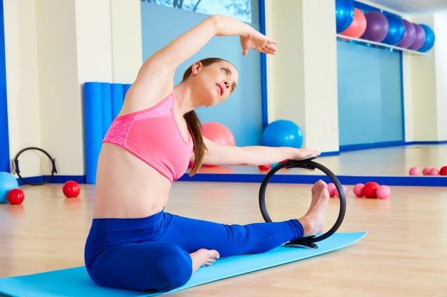 Une femme pratiquant le pilates avec un anneau de gymnastique