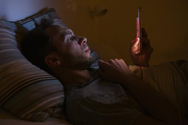 Sportif regardant son téléphone avant de dormir