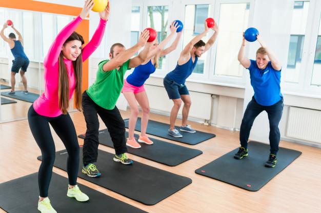 groupe de sportifs réalisant un échauffement gym douce en cours collectif