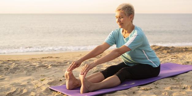 femme pratiquant la gym douce sur la plage avec des exercices de stretching