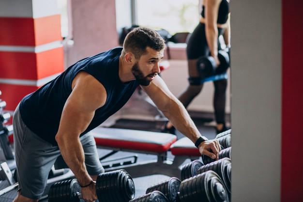 Un homme s'échauffe avant de réaliser un exercice de musculation pour le dos