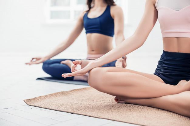 2 femmes s'échauffent avec du yoga avant de pratiquer les sports de combat