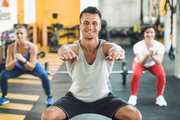 Une groupe de 3 personnes en train de s'échauffer avant un cours de fitness