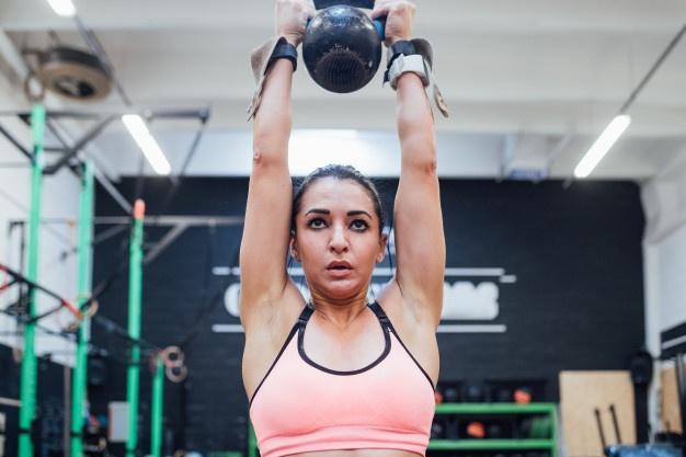 une jeune femme pratique le cross training  et réalise une variante avec kettlebell d'un clean and jerk
