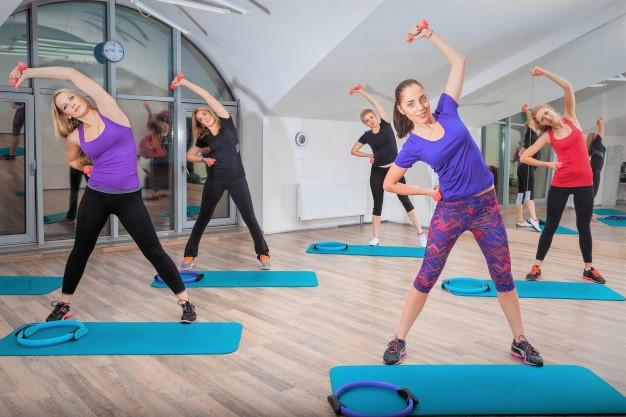 un cours collectif d'aérobic utilisant du matériel de fitness