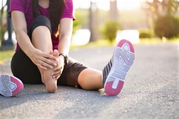une femme assise au sol après s'être fait une entorse