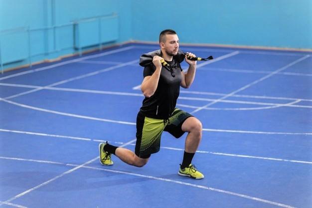 un homme réalisant des fentes marchées avec un bulgarian bag pour renforcer ses jambes